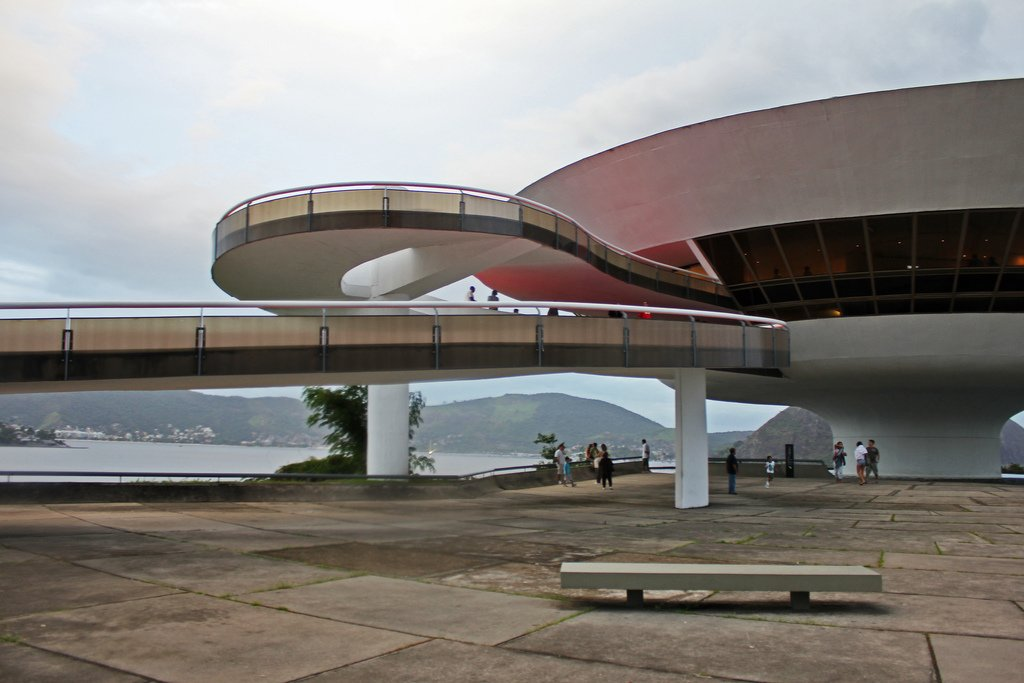 "Niterói Contemporary Art Museum  Rio de Janeiro, Brazil (1996)  ""A flower that rises from the rock"" is how Niemeyer described this organic, saucer-like structure, a home for art and design that boasts beautiful views of Guanabara Bay. An inviting red walkway snakes up towards the entrance towards the main cupola. Photo by Rosa Menkman.  Photo 5 of 10 in Design Icon: Oscar Niemeyer"