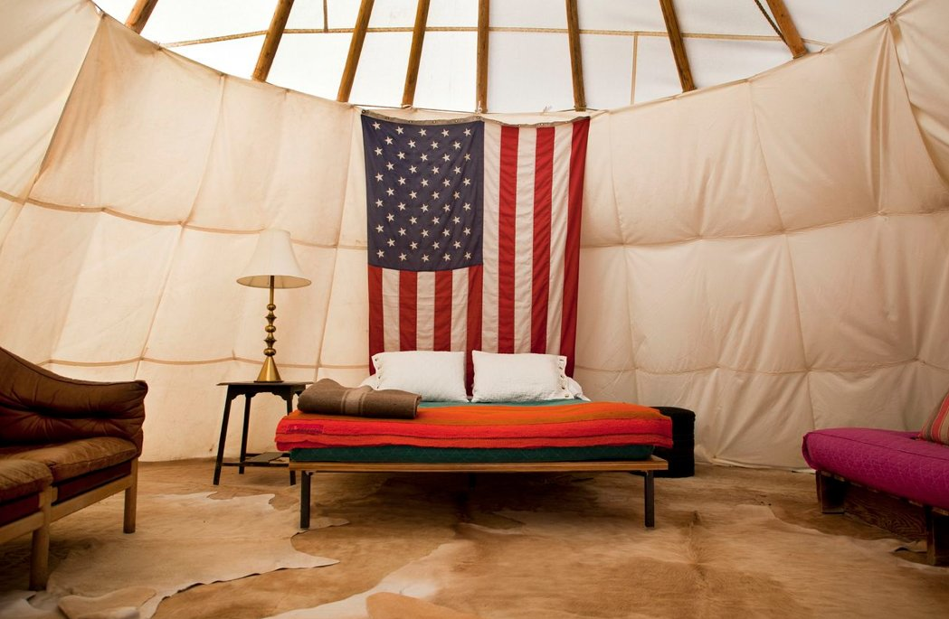 This interior shot of one of El Cosmico's teepees pairs life on the road with the American dream. Tagged: Bedroom, Lamps, Night Stands, Rug Floor, and Bed.  Photo 3 of 9 in Hotels We Love: El Cosmico Hotel in Marfa, Texas
