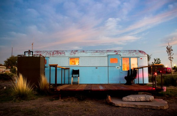 A sky-blue vintage trailer blends in with the sky.