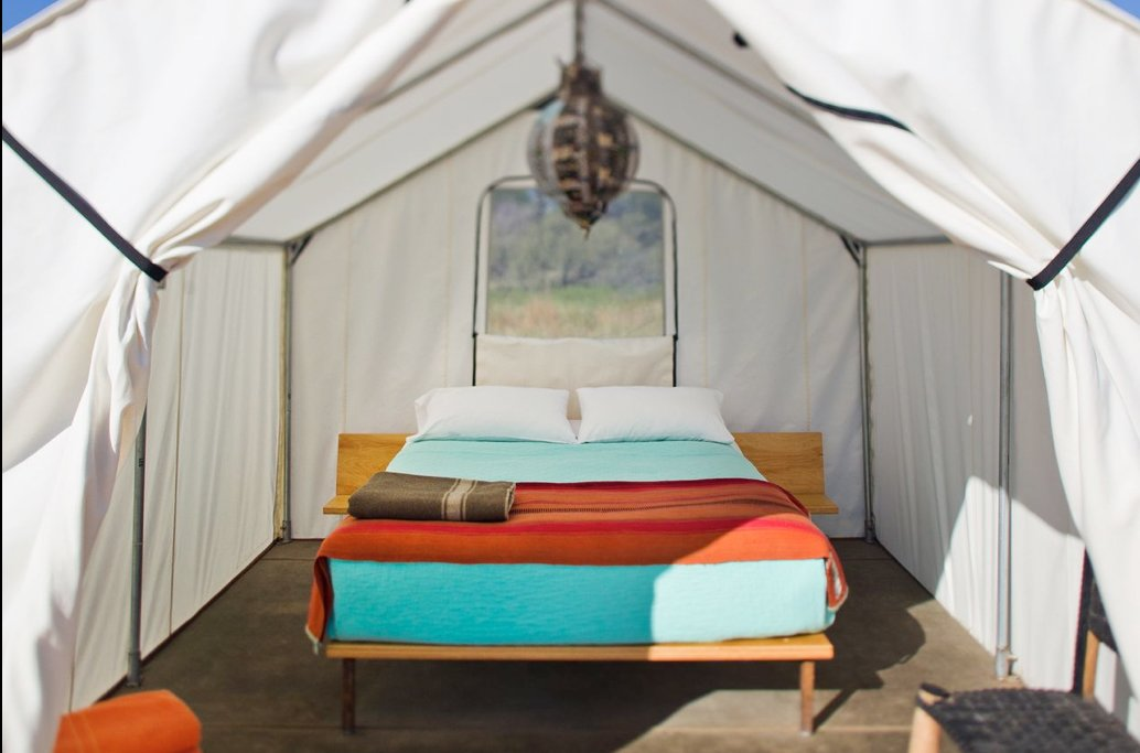 Brightly colored sheets and a central pendant lamp show this tent to its best advantage.  Photo 6 of 9 in Hotels We Love: El Cosmico Hotel in Marfa, Texas