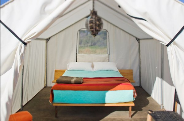 Brightly colored sheets and a central pendant lamp show this tent to its best advantage.