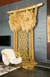 "Jonathan Adler and Simon Doonan's Shelter Island Vacation Home - Photo 6 of 10 - Andy Harman's macramé Owl punctuates the living room with a California-craft sensibility while the midnight-blue brick imbues the space with a ""German-Brutalist-1960s kind of feel,"" says Adler. ""It gives the room a nice architectural gravitas."""