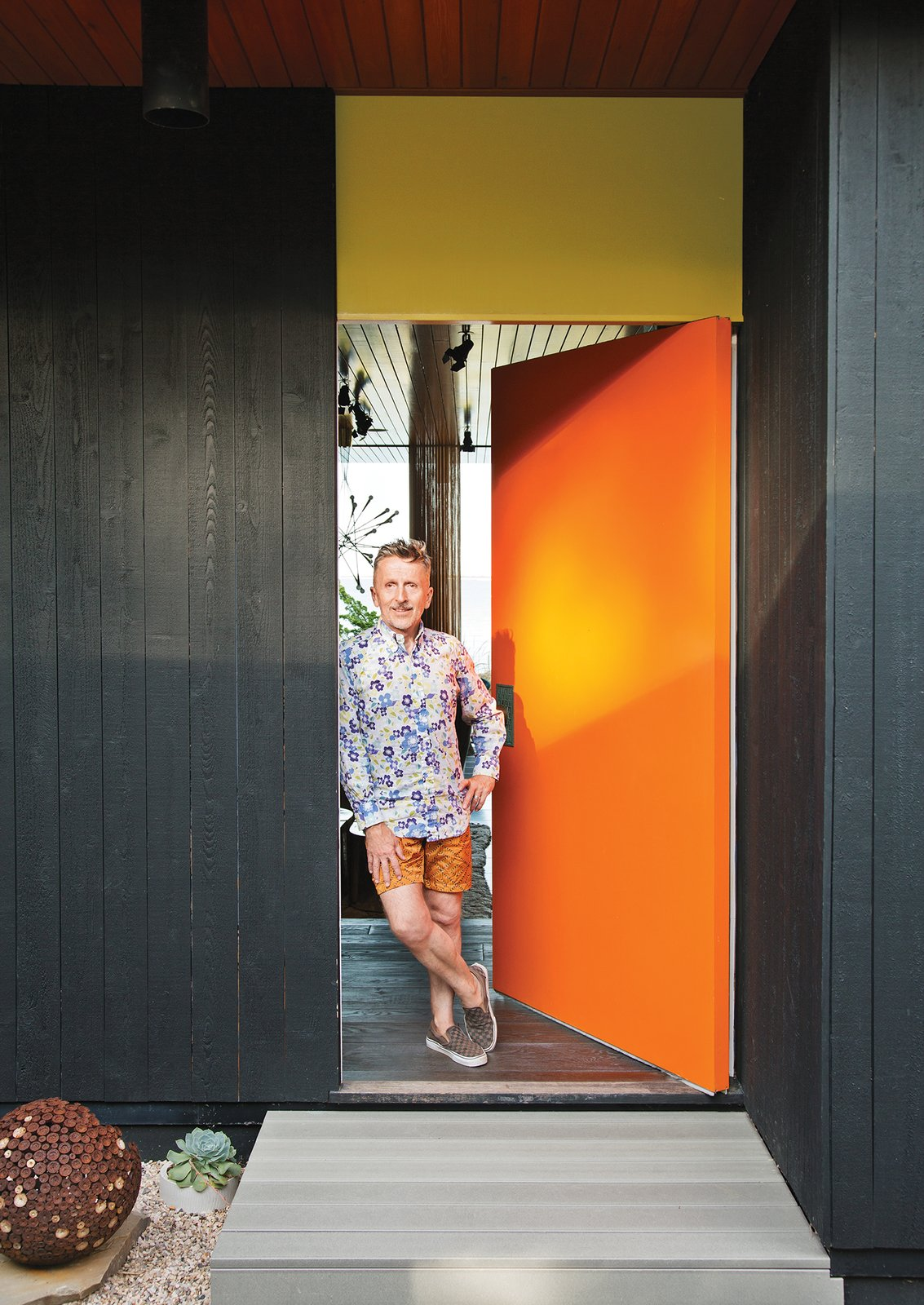 "Doonan stands next to the front door.  ""We have flamboyance, and we're not inhibited about anything. Gray Organschi gave [the house] that intellectual rigor needed to make it beautiful. We were well matched.""—Resident Simon Doonan Tagged: Doors, Exterior, and Swing Door Type. Jonathan Adler and Simon Doonan's Shelter Island Vacation Home - Photo 7 of 10"
