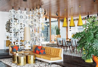 "Jonathan Adler and Simon Doonan's Shelter Island Vacation Home - Photo 5 of 10 - ""The vibe feels cozy even though the living room is quite grand,"" Adler says. He made the room divider out of concrete and integrated the sofa with the step. Lee Jofa fabric covers the dining chairs and the pendants are vintage."