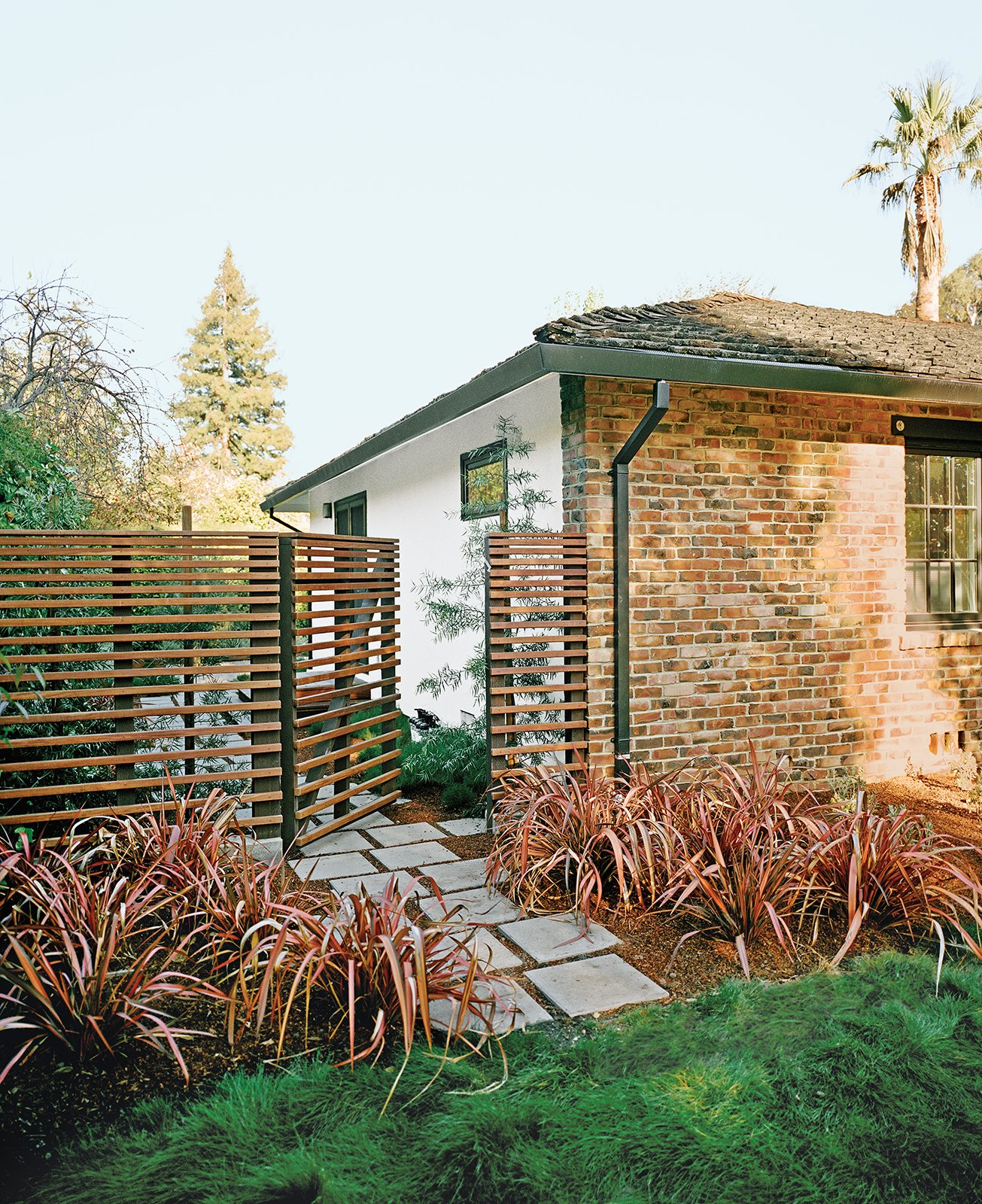 "Cox says he and Persin ""went on an ipe run"" after committing to the material for the deck, using it to build the slatted fence around the backyard. Rainbow Warrior New Zealand flax, a perennial, complements the material, while off-the-shelf pavers helped keep costs down.  30+ Best Modern Fences by William Lamb from Bay Area Ipe-Clad Backyard Getaway"