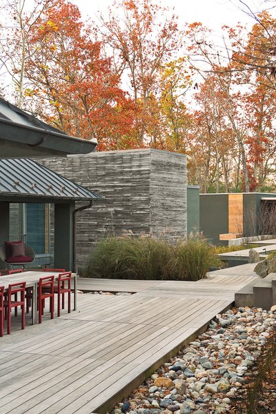 The dining table, a custom design by Formwork, and red Non chairs by Komplot complement the addition's cypress cladding.