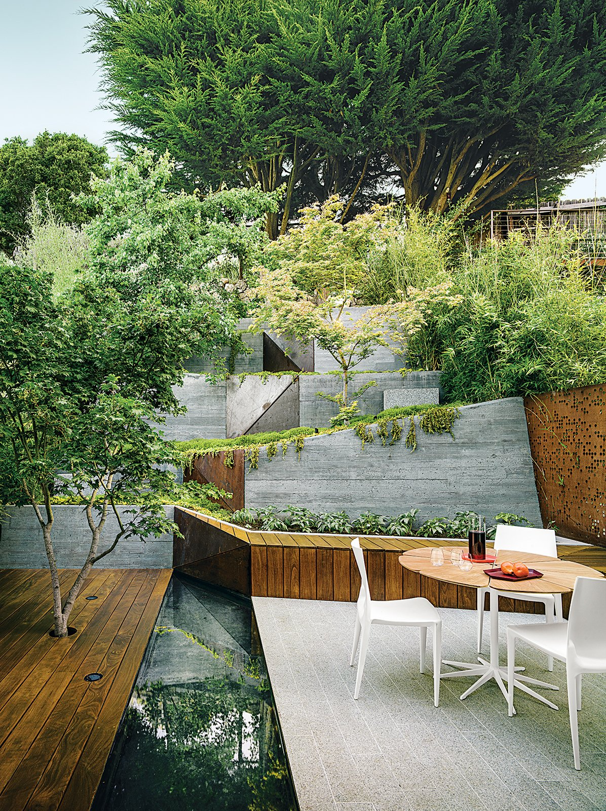 A maple tree grows through an ipe deck in the garden that Mary Barensfeld designed for a family in Berkeley, California. A reflecting pool separates it from a white-granite patio, which is furnished with a Petal dining table by Richard Schultz and chairs by Mario Bellini. Tagged: Outdoor, Small Patio, Porch, Deck, Back Yard, Shrubs, Trees, and Raised Planters.  Botanical  Space by Brian Perez from How to Make Your Tiny Yard Feel Spacious