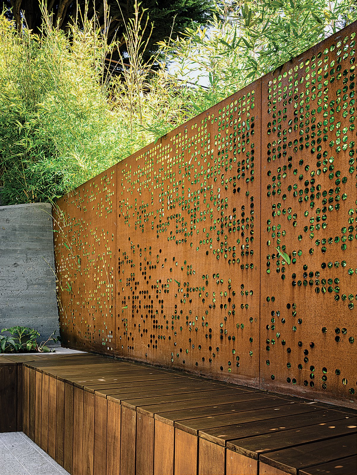 With input from her clients, Barensfeld used a computer to generate the circular patterns that were carved into a pair of Cor-Ten steel screens with a water-jet cutter. The perforations allow light and the green of the surrounding Koi bamboo to filter into the space while preserving privacy. Tagged: Outdoor and Metal Fences, Wall.  Photo 3 of 4 in An Architect Sculpts Out a Tadao Ando-Inspired Backyard