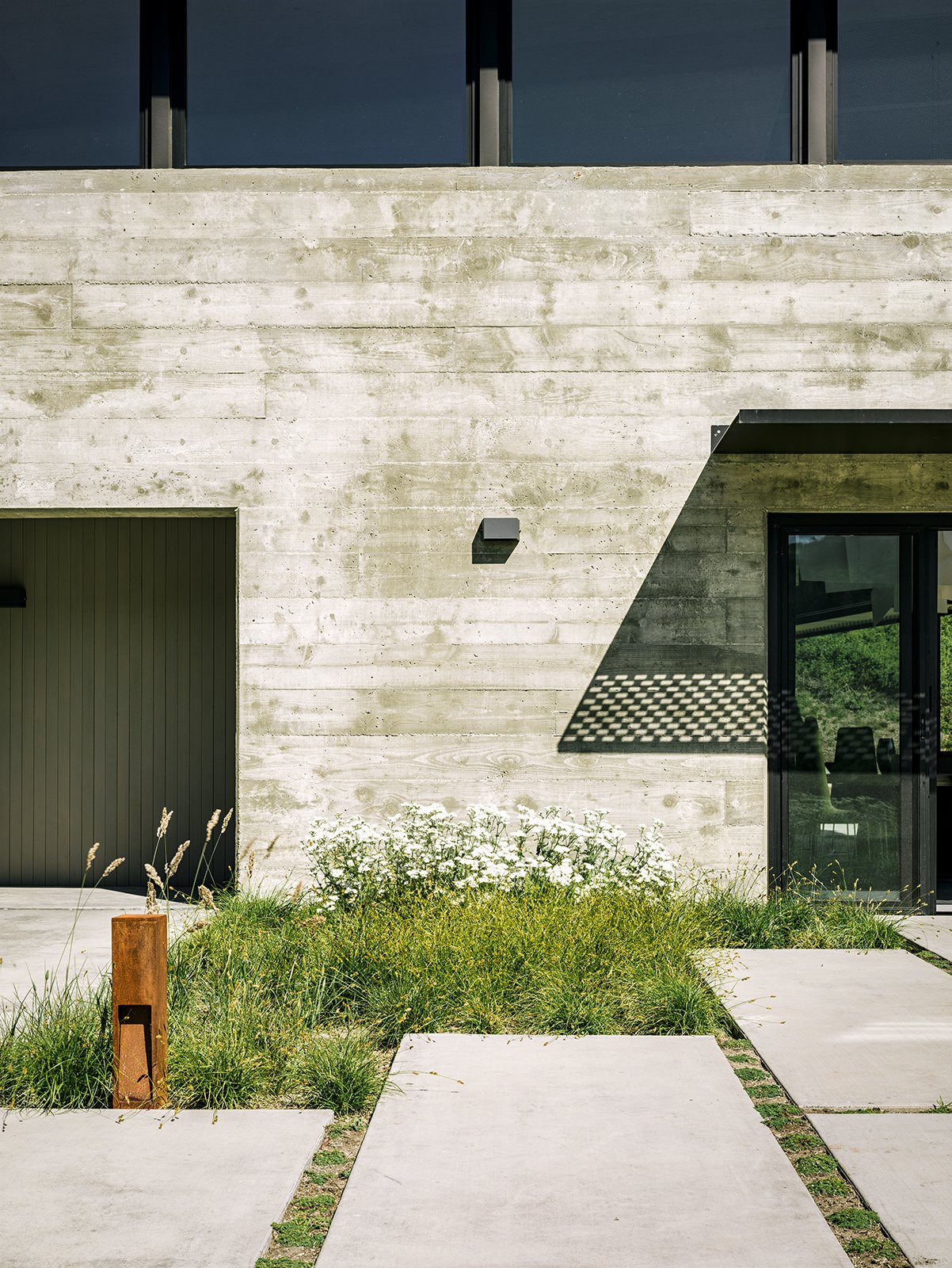 """More native grasses set the tone near the generously sized concrete pavers leading to the entrance. """"We didn't want the planting to feel like a country cottage garden—that would have felt disconnected with the view behind it,"""" Trainor says. Landscapes Designed with Native Plants by Zachary Edelson"""