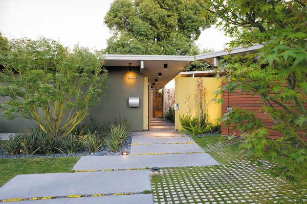 An ipe fence and a neon-yellow resin screen fashioned from recycled acrylic panels draw visitors toward the entrance to the Kreadens' renovated Eichler house.