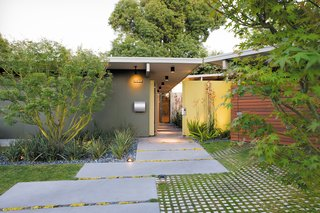 7 Modern Eichler Renovations in California - Photo 4 of 8 - An ipe fence and a neon-yellow resin screen fashioned from recycled acrylic panels draw visitors toward the entrance to the Kreadens' renovated Eichler house.