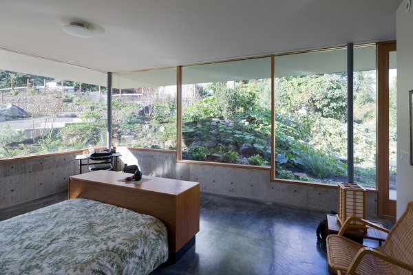 In the master bedroom, stepped windows framed by Douglas fir mullions rest on low concrete walls that are flush with the easy-to-maintain, hand-troweled concrete floor. The platform bed is from Scan Design and the rattan chair is from Ikea.