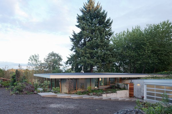 The driveway leads down a gentle slope to the garage, which is partially tucked into the earth, covered by a green roof, and fronted by a ramp leading to the entrance. Alexander Prideaux of Aurora Landscape helped integrate the house with the site.