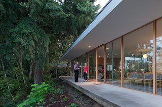 "Surrounded by a canopy of trees, the house is bordered by a deep overhang that matches the width of the concrete terrace. ""What I like is that the decks and the courtyard are visually part of the house, but they're outdoor spaces,"" says Ted. Heid worked with Curtis Bosworth and John Weed of WBS Construction on the project."
