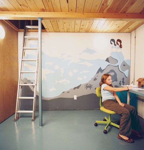 Eve works at the desk in her double-height bedroom. Vogt's mythically aquatic-themed mural reflects both the taste of a young girl and the pared-back aesthetic of any modern enthusiast.