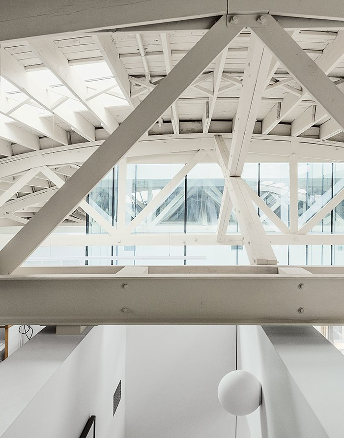 Architects William Neburka and Carrie Strickland set off some spaces with walls that stop shy of the bowstring trusses to preserve an overall sense of openness.  Photo 8 of 12 in This Light-Filled Industrial Renovation Plays Host to Live Music