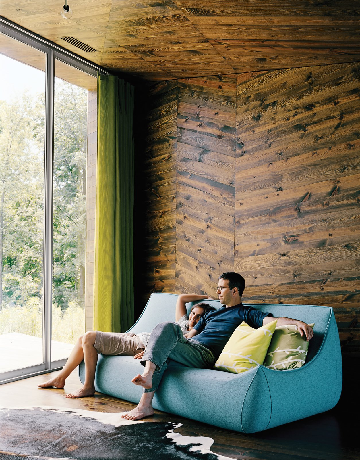 In the warm interior of the X House in Hennepin, Illinois, Diane Pascal and Thomas Richie enjoy the view from their boiled-wool Ligne Roset couch in the main living area, where wood paneling on the ceiling and walls mirrors the topography of the landscape. A gauzy green curtain adds a moment of color to the scheme.
