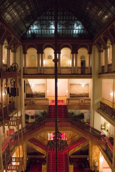 """Interior of the Grand Budapest Hotel. Anderson stumbled upon the Görlitzer Warenhaus, an abandoned department store in Görlitz. This """"tremendous find,"""" according to Stockhausen, made building an interior possible within his budget, and the production crew build an entire hotel lobby inside."""