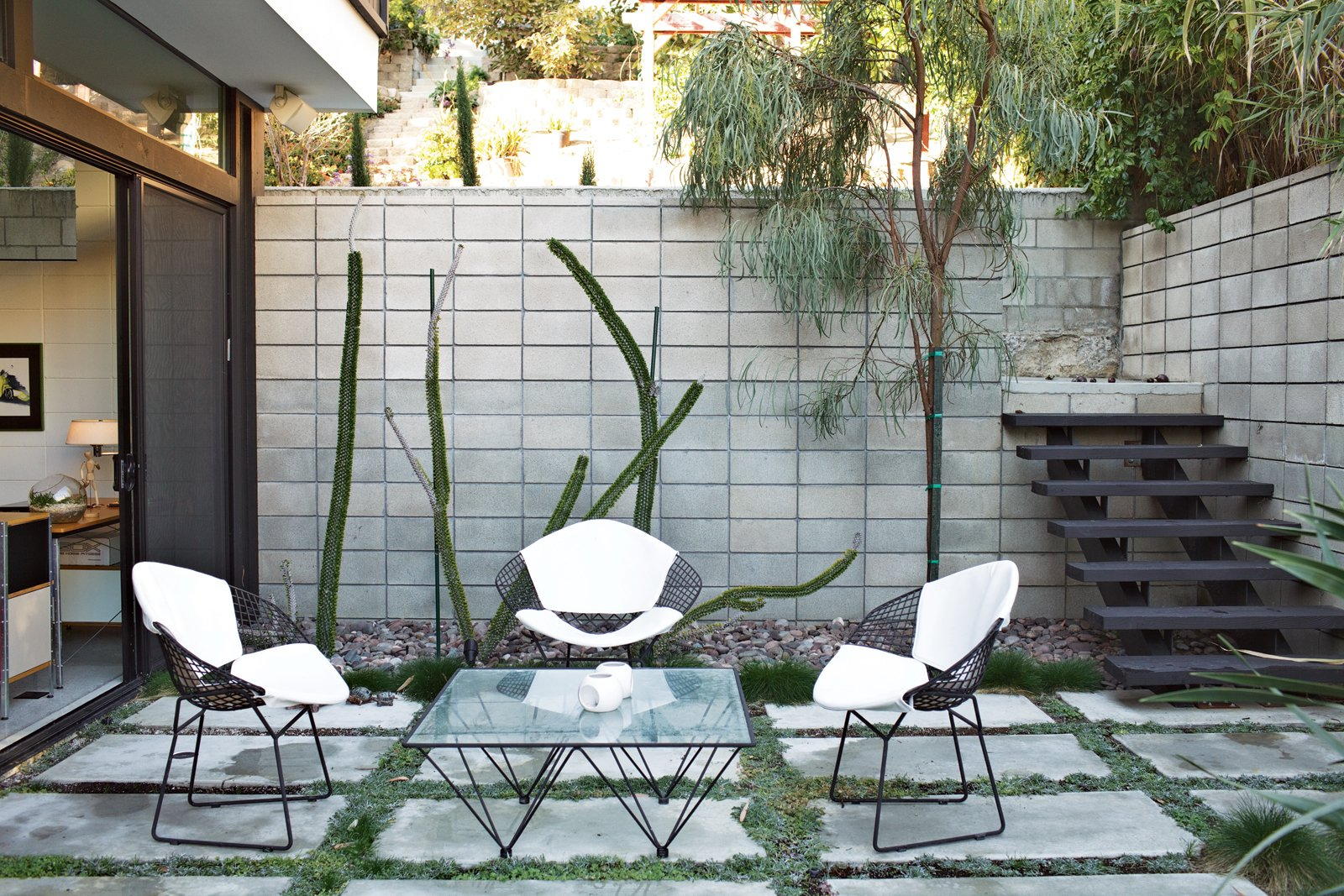 Outside, a set of Bertoia chairs offer an appealing perch around a vintage glass-and-metal table. Tagged: Outdoor, Small Patio, Porch, Deck, Concrete Patio, Porch, Deck, and Concrete Fences, Wall.  Photo 11 of 13 in The First LEED Gold-Certified Family Home in San Diego