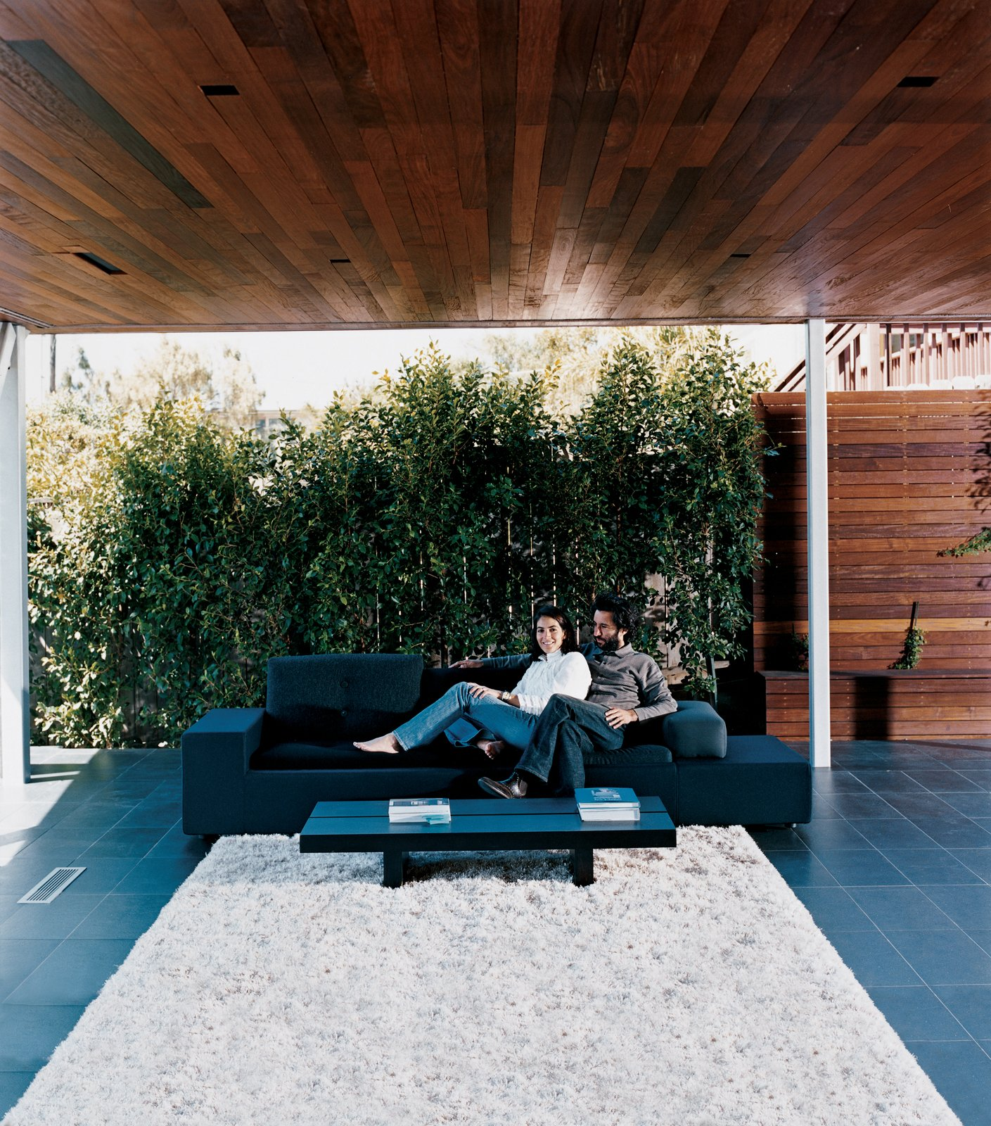 Sebastian and Maricarmen take in the scenery from the comfort of their exposed living room. The couple sits on a Polder sofa by Hella Jongerius for Vitra. Tagged: Outdoor and Back Yard.  Photo 6 of 7 in Sebastian Mariscal's Wood Architecture from Double the Pleasure