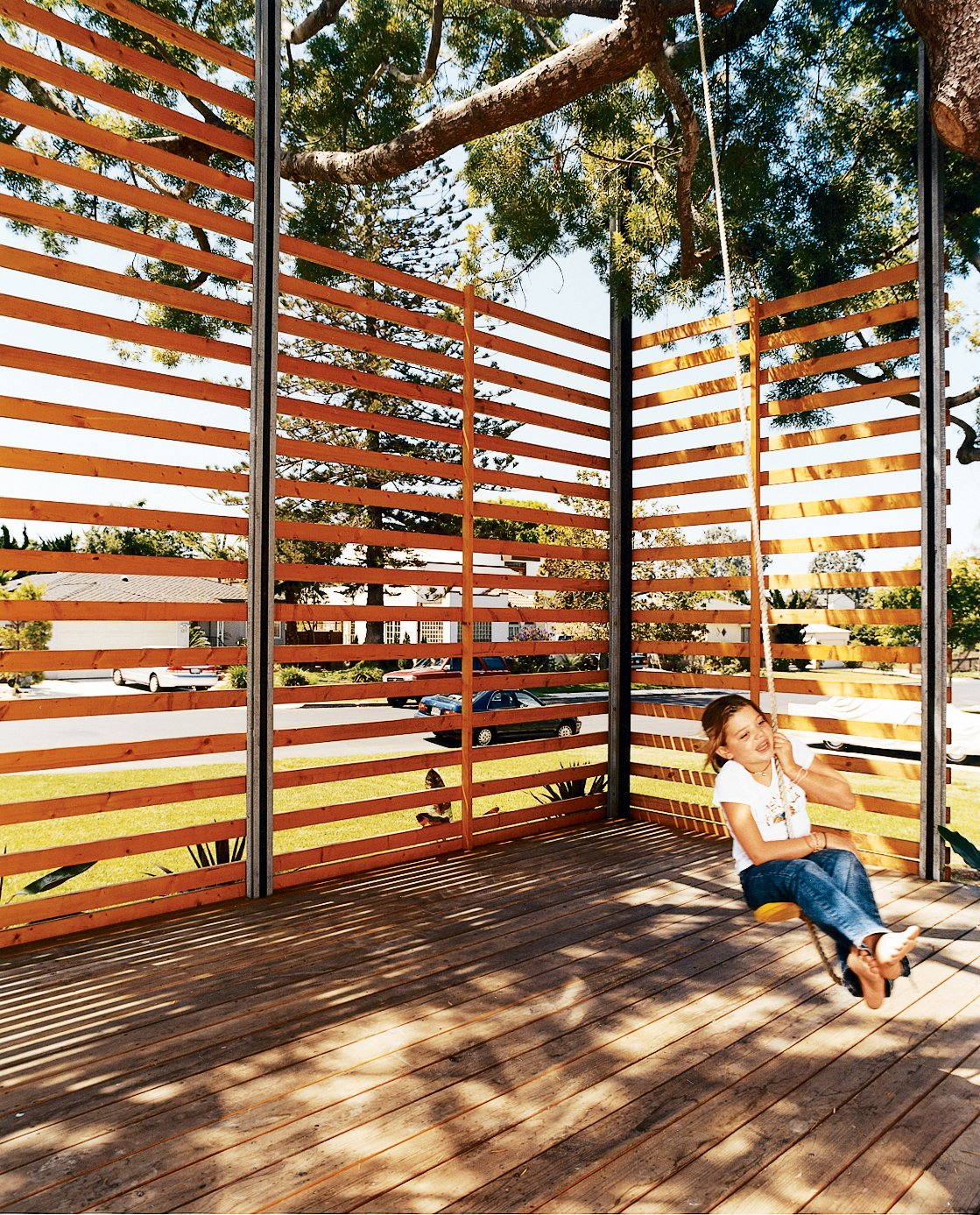 Gabriella swings on the rope swing hung from the podocarpus tree. The twenty-foot-tall, steel-framed, custom-built wood screen provides enough privacy to give the outdoor space the feeling of a room, with the 50-year-old polocarpus tree acting as a roof.  Photo 7 of 7 in The Family Tree