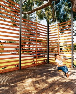 The Family Tree - Photo 7 of 7 - Gabriella swings on the rope swing hung from the podocarpus tree. The twenty-foot-tall, steel-framed, custom-built wood screen provides enough privacy to give the outdoor space the feeling of a room, with the 50-year-old polocarpus tree acting as a roof.