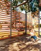 Gabriella swings on the rope swing hung from the podocarpus tree. The twenty-foot-tall, steel-framed, custom-built wood screen provides enough privacy to give the outdoor space the feeling of a room, with the 50-year-old polocarpus tree acting as a roof. Photo  of Design Guide: San Diego  modern home