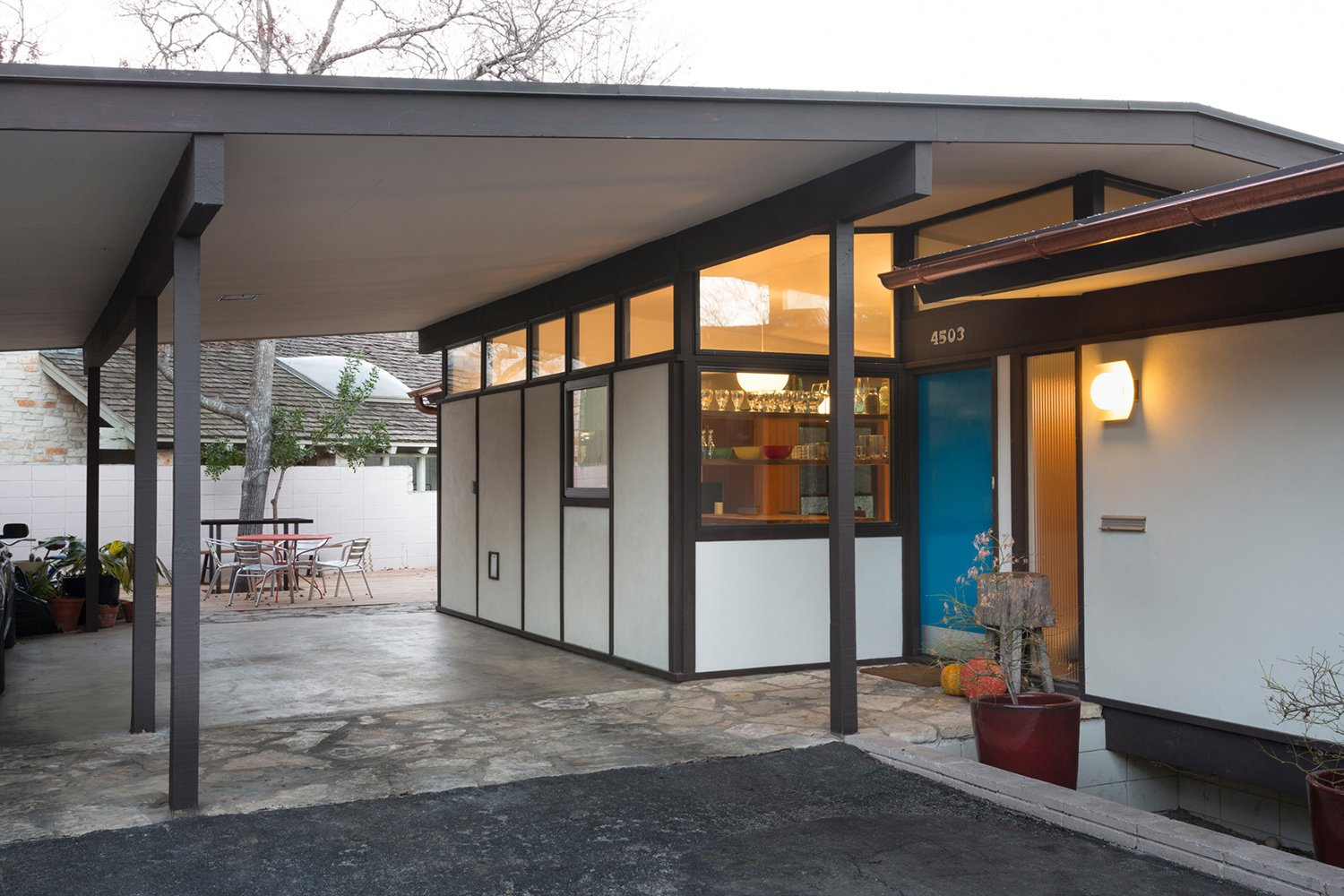 A close-up of the renovated exterior shows the home's new, brightly-colored door in relief of the new kitchen window, whose floating shelves are just visible. Selected by Sloan Houser, the door's shade of turquiose is similar to Benjamin Moore's Americana, although with stronger hints of green.  47+ Midcentury Modern Homes Across America by Luke Hopping from Midcentury Renovation in Austin