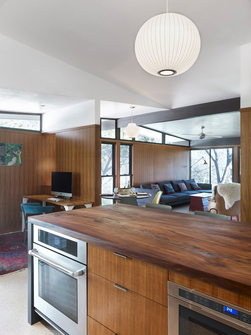 A post-renovation view of the kitchen shows it opening into the family room. Replacing the former white cabinets are Island drawer fronts and wall panelling of teak wood and reclaimed American elm countertop, milled by Vintage Material Supply. The differing grains of the teak veneers and elm countertop vadd complexity and rhythm to the kitchen's wood motif. Stuc Pierre plaster ceiling selected by the homeowner, Sloan Houser, adds an airy feel to the opened space.  Photo 11 of 14 in Inspired Indoor Teak Looks from Midcentury Renovation in Austin