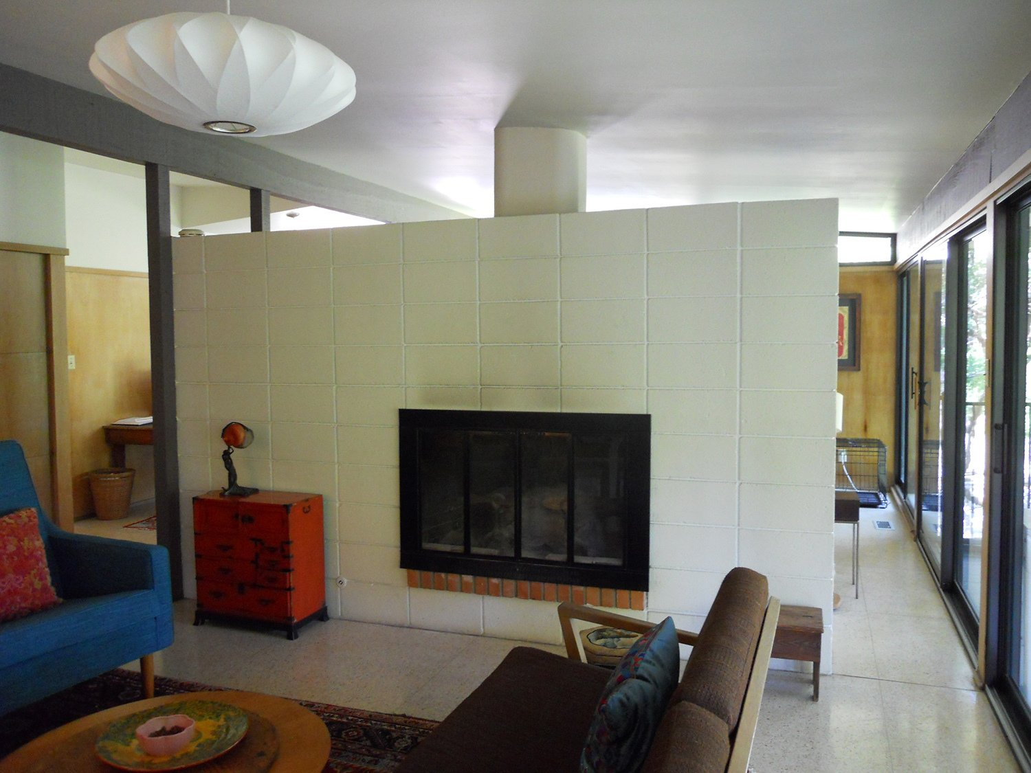 BEFORE: Looking disjointed, the living room in the pre-renovation Houser home is an alienated space, occluded from the natural light entering the spaces just beyond. Midcentury Renovation in Austin - Photo 11 of 13