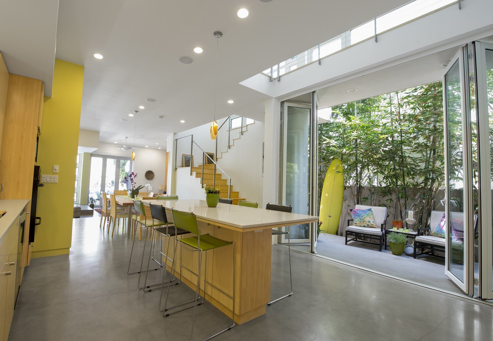"""The kitchen and dining area opens onto a patio. Photo by Ken Pagliaro Photography. Tagged: Kitchen, Concrete Floor, Recessed Lighting, Ceiling Lighting, and Wood Cabinet.  Photo 1 of 8 in A Sustainable """"Case Study"""" House in California"""