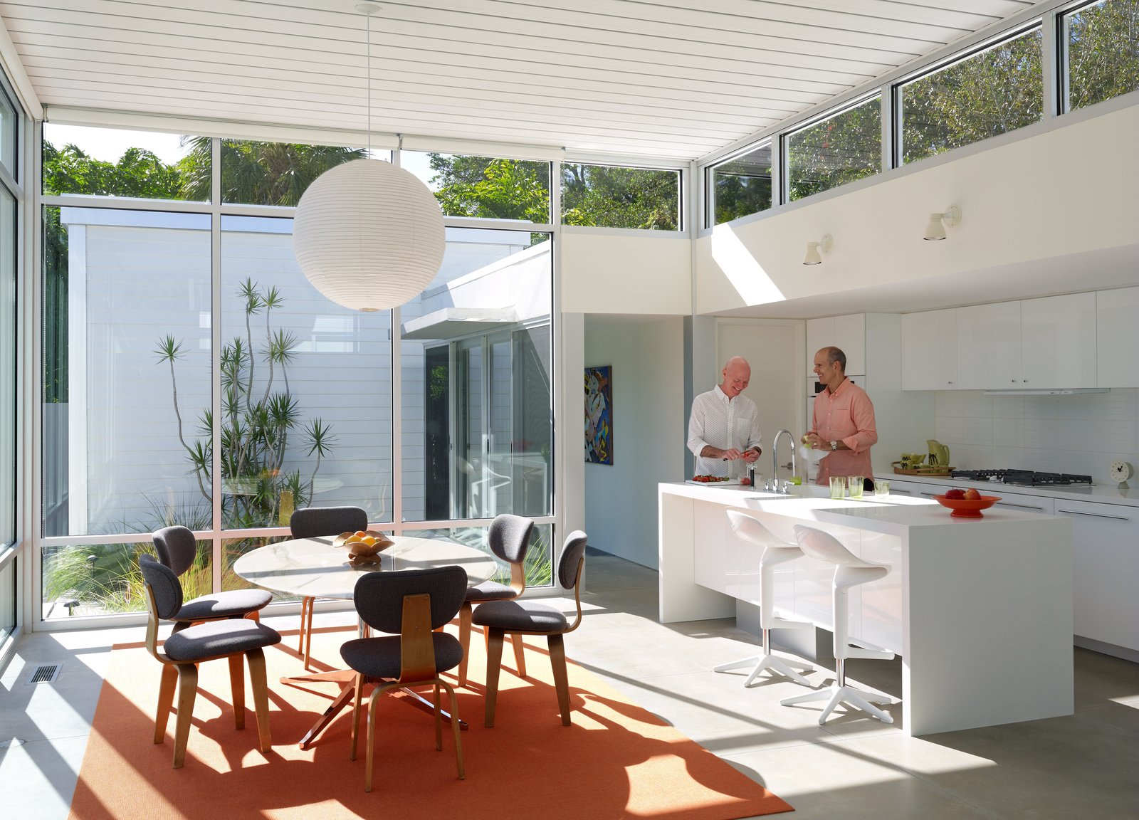 In the kitchen, Pirman and Tetreault gather around a custom Corian island with a Tara faucet by Dornbracht. Vintage Cees Braakman Combex series chairs and a marble Florence Knoll table bring natural materials to an architectural shell built from concrete, glass, and steel. Tagged: Kitchen and White Cabinet.  Midcentury Homes by Dwell from This Sparkling New Home Is a Perfect Remake of Classic Sarasota School Modernism