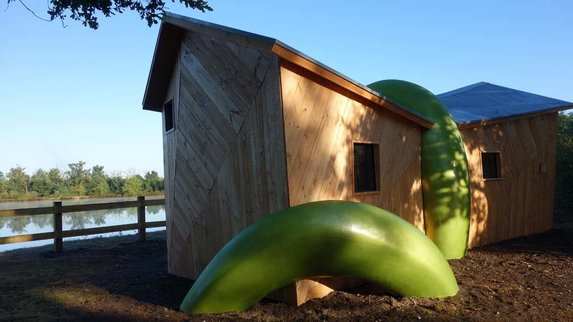 """La vouivre"" is a wood hut enclosed by a magical, anaconda-sized green snake concieved and built by Zebra3."