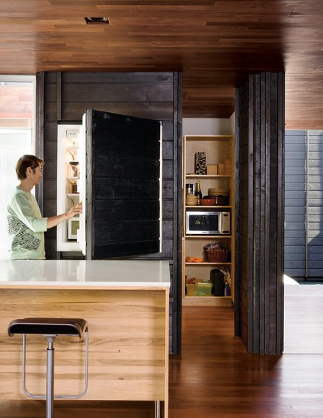While most of the ground level is given over to the large open living and dining area, it also includes a small pantry, office, and Japanese bathroom. An integrated Sub-Zero refrigerator is almost unnoticeable behind its charred cedar cladding.