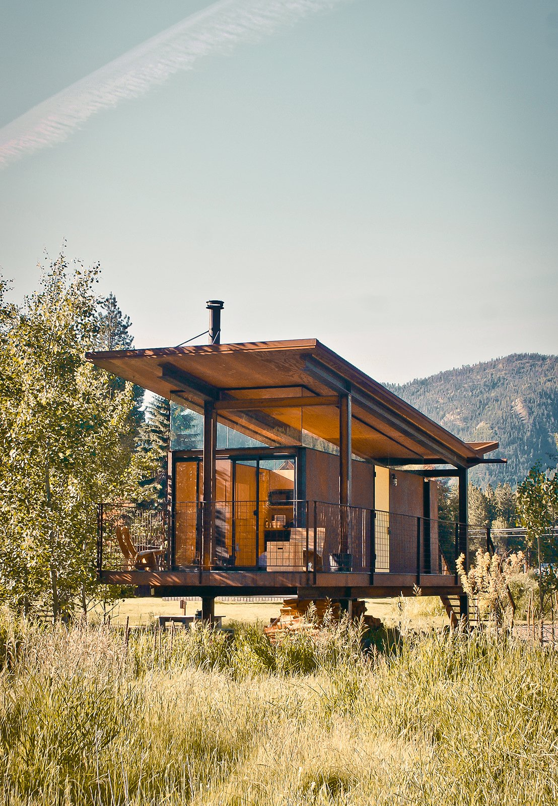 """The steel-clad Rolling Huts designed by Olson Kundig Architects in Manzama, Washington, sit lightly on the land thanks to wheels that allow the tiny residences to """"hover"""" above the site, optimizing views of the landscape. Photo by Derek Pirozzi. Tagged: Exterior, Cabin, Butterfly, Metal, Metal, and Glass.  Best Exterior Butterfly Cabin Photos from Olson Kundig Houses"""