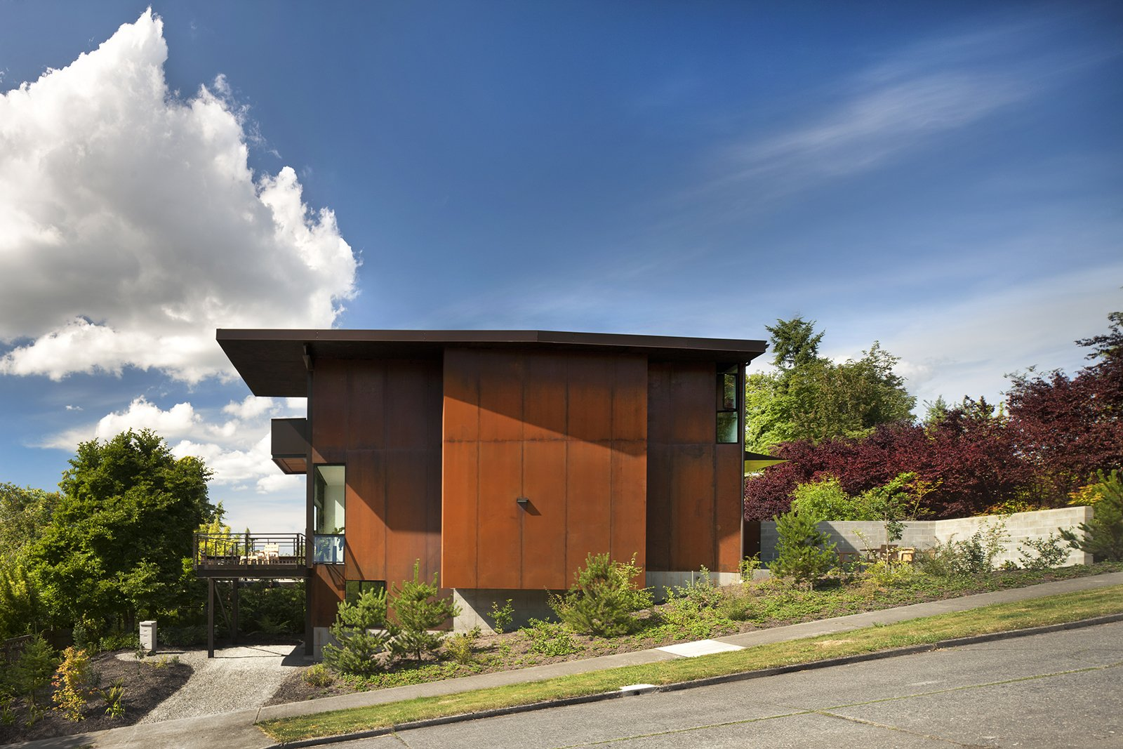 The Hammer House in Seattle is clad in weathered steel panels, which provide privacy from the busy street. Natural light enters from a glass-walled bay directly behind the opaque wall. Photo by: Nic Lehoux Tagged: Exterior, Metal Siding Material, and House.  5 Ways to Use Steel in Modern Homes by Allie Weiss from Olson Kundig Houses