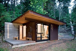 "101 Best Modern Cabins - Photo 68 of 101 - This 191-square-foot cabin near Vancouver and its glass facades ""forces you to engage with the bigger landscape,"" architect Tom Kundig says, but it seals up tight when its owner is away. The unfinished steel cladding slides over the windows, turning it into a protected bunker. Read the full story here."