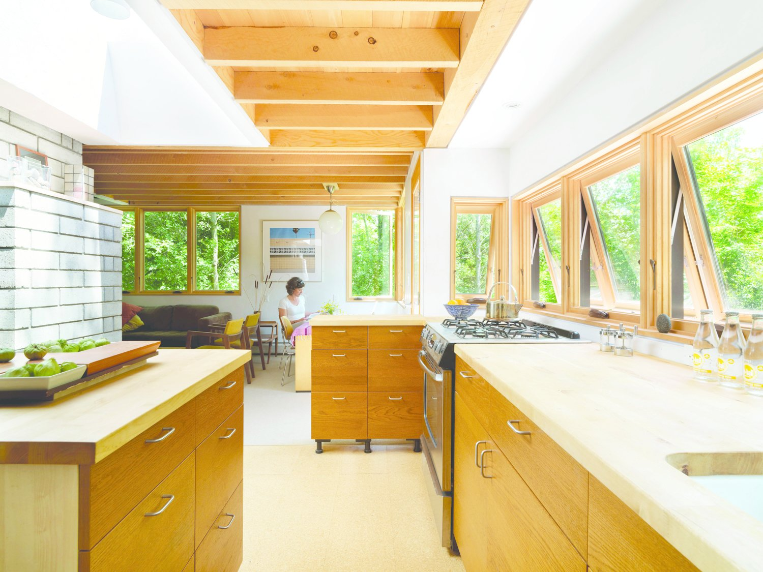 Daylight adds to the warm ambiance of the wooden millwork of the Nature Preserve House kitchen.