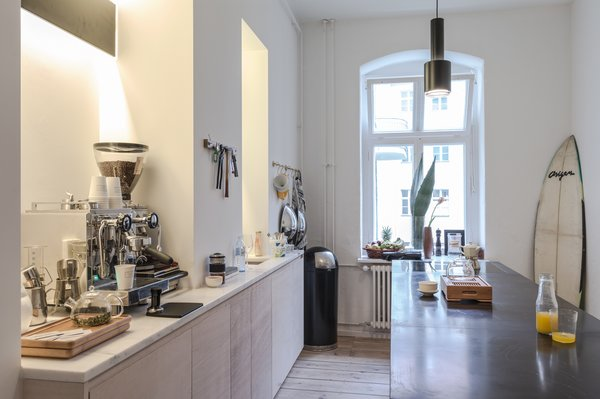 Kitchen of the Freunde von Freunden X Vitra ApartmentRide the wave: The sleek, open kitchen, centered around the custom black marble island with none-too-subtle Southern California callouts like the surfboard in the corner, is Frede's favorite room. The kitchen fixtures and countertops are by Miele and Dornbract. Photo by Steve Herud