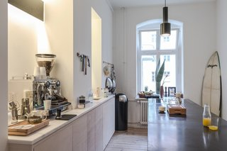 Freunde von Freunden and Vitra's Berlin Apartment - Photo 5 of 9 - Kitchen of the Freunde von Freunden X Vitra ApartmentRide the wave: The sleek, open kitchen, centered around the custom black marble island with none-too-subtle Southern California callouts like the surfboard in the corner, is Frede's favorite room. The kitchen fixtures and countertops are by Miele and Dornbract. Photo by Steve Herud