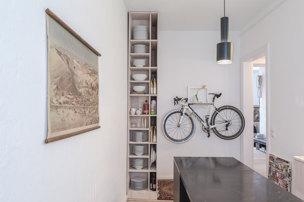 Kitchen of the Freunde von Freunden X Vitra ApartmentArchitect Etienne Descloux adjusted the original bathroom design to provide more space for storage in the kitchen. Bike by Mikili, flowers by Marsano.Photo by Steve Herud