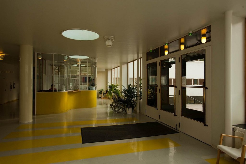 "Paimio Sanatorium (Paimio, Finland: 1933)  Aalto designed this sanitorium for tuberculosis patients to be a ""medical instrument,"" a structure actively engaged in the healing process. Small touches, such as personal wash basins, glare-resistant interior paints and large balconies to soak up sunshine, came from his shrewd and empathetic observations (supposedly sick at the time himself, he realized that hospital rooms should have a ""horizontal"" layout, since patients would spend most of their time in bed).  The furniture Alvar and his wife Aino created for the building can still be purchased through Artek.   (Credit: LeonL, creative commons) Design Icon: 10 Buildings By Alvar Aalto - Photo 9 of 11"