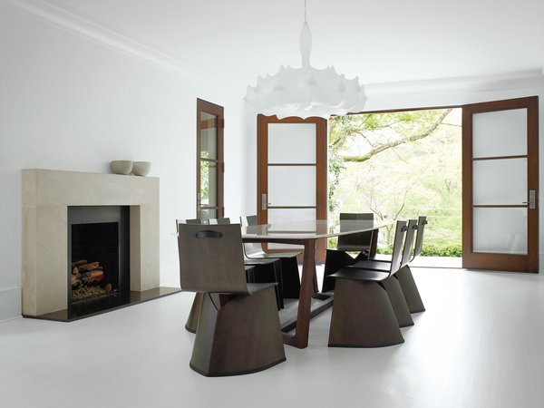 "Konstantin Grcic's Venus chairs for ClassiCon surround a table by Poliform in the formal dining room. Hill selected the Flos chandelier designed by Marcel Wanders for its ""Old World reverence."" The sleek fireplace mantel was designed by Hill and cobbled together onsite from three solid slabs of limestone."