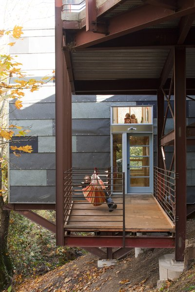 A porch at the bottom floor level serves as a rest space, play area, and work spot when Hale pulls out his tools. The horizontal window above connects the first floor to the deck so Hale and Edmonds can keep a watchful eye on the girls when they play outside.