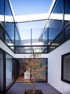 These Courtyards Bring Indoor/Outdoor Living to 10 Modern Homes - Photo 2 of 10 - The home's forms, which are masked by the cantilevered entrance, become apparent once one enters the central courtyard. The roofline can be seen fluctuating as one goes from front-to-back. The memorial tree, around which the courtyard and home are built, will continue to grow in coming years.