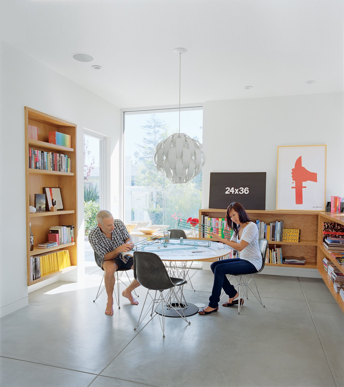 """The dining room is meant to be a flexible space for eating or dancing. """"One of the most important things for me,"""" explains Grunbaum, """"is how a house feels. It has to be a place where you don't want to leave."""" The Cyclone table is by Isamu Noguchi for Knoll and the pendant lamp is by Lightoiler.  Photo 3 of 11 in Daft Punk Could Play at This House from Photographer Q&A: Ye Rin Mok"""