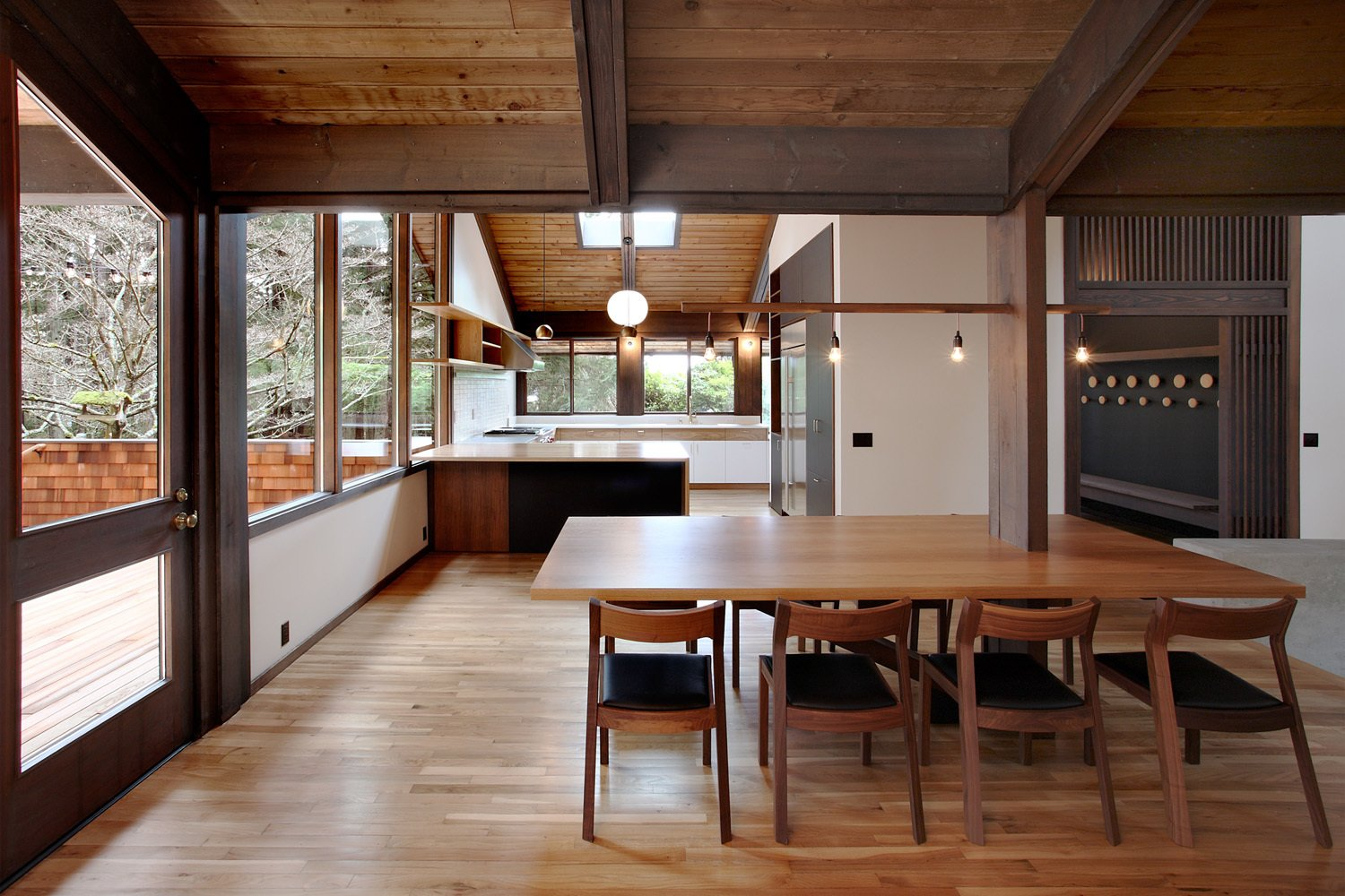 """The light fixtures, a string of dangling lights seen above the dining table, emulate what SHED Architects principal Thomas Schaer calls Zema's """"builderly"""" style: straightforward and unpretentious. The wooden screens, seen top right, are all-new to the house but follow Zema's Japanese-inspired style.  47+ Midcentury Modern Homes Across America by Luke Hopping from House of the Week: Midcentury Modern Reboot in Washington"""