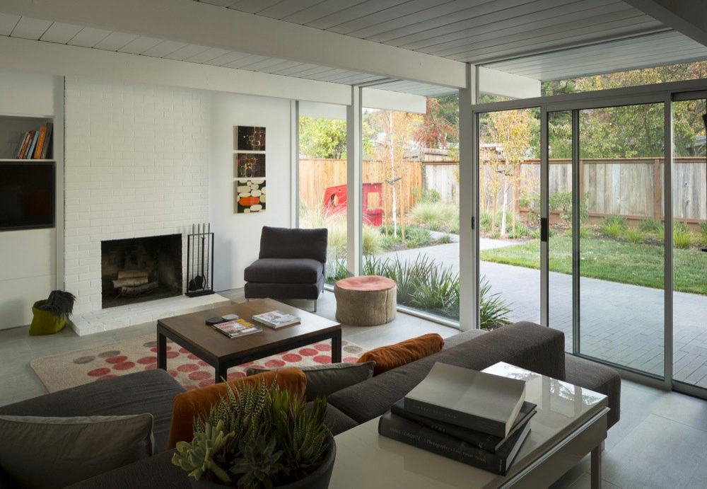 The expansive windows facing the home's backyard also amplify light in the living room. Grounding grey and russet brown furnishings meld the open, airy space with the light brown fencing just visible outside. Photo by: Scott Hargis