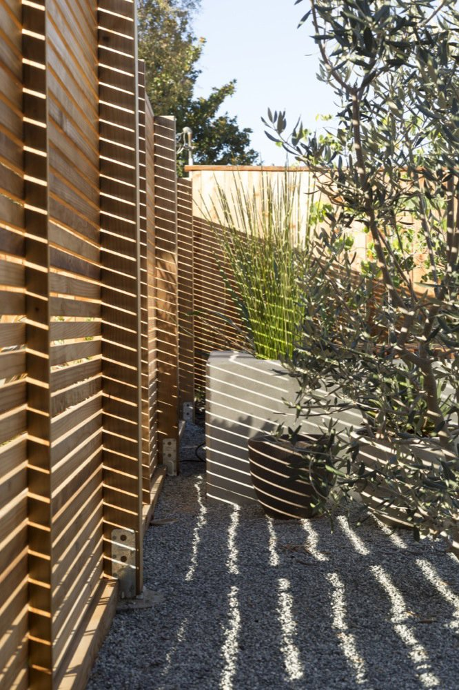 A key aspect of the renovation was ensuring the privacy of the resident, whose frontyard formerly exposed the home to the road. At five feet high, this slatted fencing encloses just enough: providing privacy without isolating the home from its setting. Photo by: Scott Hargis