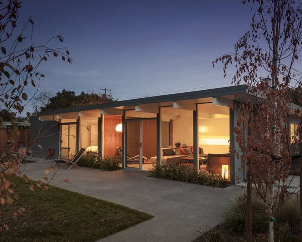A wall of windows provides a smooth transition between indoor and outdoor spaces in this renovated home. Open to the fenced-in yard, the patio is as intimate as the living room and bedroom just inside. Photo by: Scott Hargis  Photo 9 of 9 in A Renovated Eichler Home in San Rafael, California